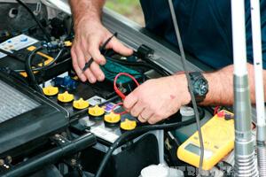 Автоэлектрик проводит диагностику аккумулятора