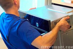 Электрик устанавливает духовой шкаф